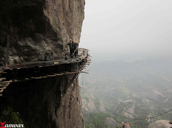 Workers build a plank road on the side of Shifou Mountain, Huna